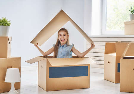Child girl in the house with a symbol of roof. Concept of housing for family. Stockfoto