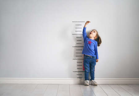 Little child is playing superhero. Kid is measuring the growth on the background of wall. Girl power concept.