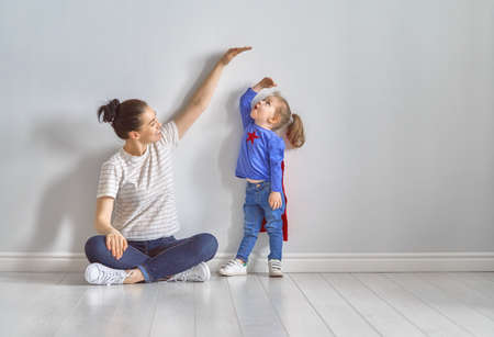 Mother is measuring growth of child daughter near empty wall. Girl in superhero costume.