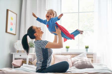 Moeder en haar kind samen spelen. Meisje en moeder in superheld kostuum. Moeder en kind plezier, glimlachen en knuffelen. Gezinsvakantie en samenzijn. Stockfoto