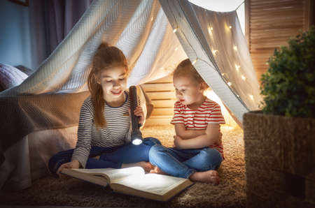 Two cute little children are reading a book with flashlights in tent. Happy girls playing at home. Funny lovely kids having fun in room.  Banco de Imagens