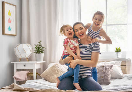 Happy loving family. Mother and  two her daughters children girls playing and hugging. 스톡 콘텐츠