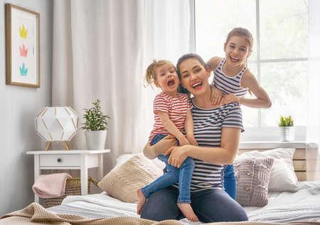 Gelukkig liefdevolle familie. Moeder en twee haar dochters kinderen meisjes spelen en knuffelen. Stockfoto - 99780695