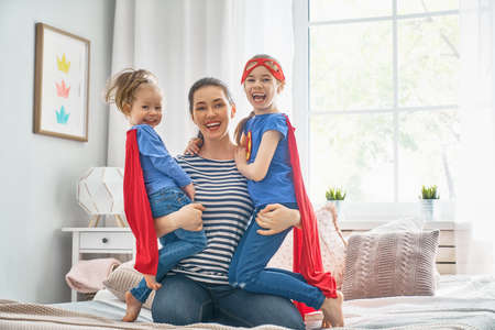 Mother and her children playing together. Mom and girls in Superhero costumes. Mum and kids having fun, smiling and hugging. Family holiday and togetherness.