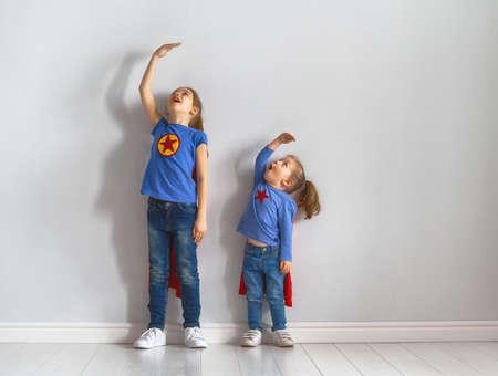 二人の小さな子供がスーパーヒーローを演じている。子供たちは壁の背景に成長を測定しています。ガールパワーコンセプト。 写真素材