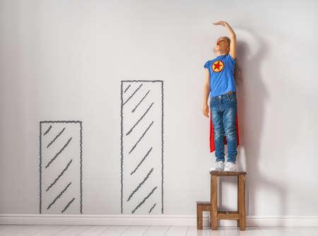 Il bambino piccolo sta giocando al supereroe. Kid sta misurando la crescita sullo sfondo del muro. Concetto di potere della ragazza.
