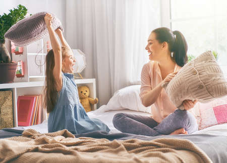 Happy loving family! The mother and her child girl are fighting pillows.  Stock Photo