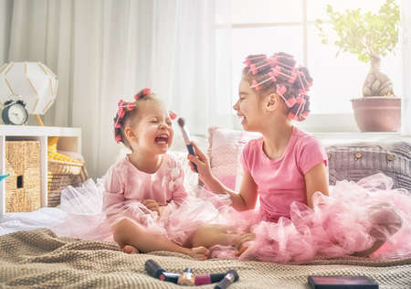 Happy childhood. Two sisters are doing hair and having fun. Children doing makeup sitting on the bed in the bedroom. Stock Photo