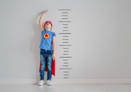 小さな子供がスーパーヒーローを演じている。子供は壁の背景に成長を測定しています。ガールパワーコンセプト。