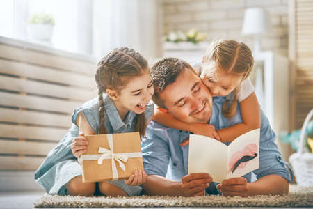Happy fathers day! Children daughters congratulating dad and giving him postcard and gift box. Daddy and girls smiling and hugging. Family holiday and togetherness. Stock Photo