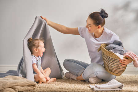 Belle jeune femme et enfant fille petite aide s'amusent et sourient tout en faisant la lessive à la maison.