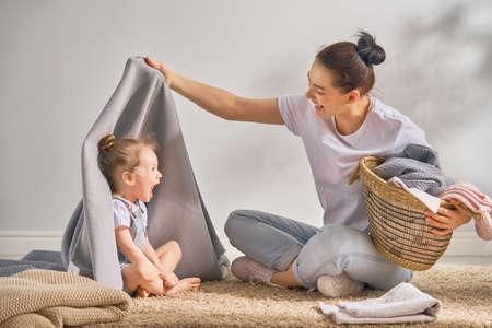Hermosa joven y niña pequeña ayudante se divierten y sonríen mientras lavan la ropa en casa.