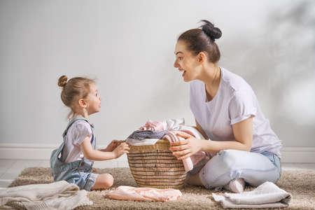 De mooie jonge vrouw en de kleine helper van het kindmeisje hebben pret en glimlachen terwijl het thuis doen van was. Stockfoto