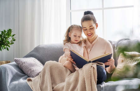happy loving family. pretty young mother reading a book to her daughter