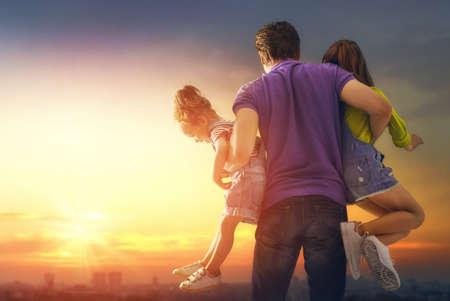 Glückliche liebende Familie. Vater und seine Töchter Kinder spielen und umarmen sich im Freien. Süße kleine Mädchen und Papa. Standard-Bild - 100973026