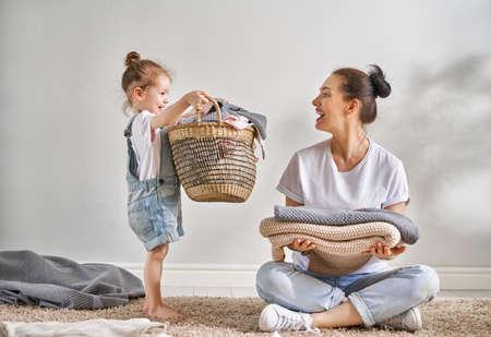 Bella giovane donna e bambina piccola aiutante si divertono e sorridono mentre fanno il bucato a casa.