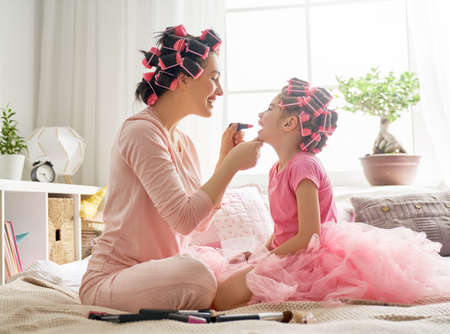 Happy loving family. Mother and daughter are doing hair and having fun. Mom and her child girl playing, kissing and hugging. Banque d'images - 101087574
