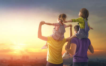 happy family at sunset. father, mother and two children daughters having fun and playing in nature. the child sits on the shoulders of his father. Stok Fotoğraf