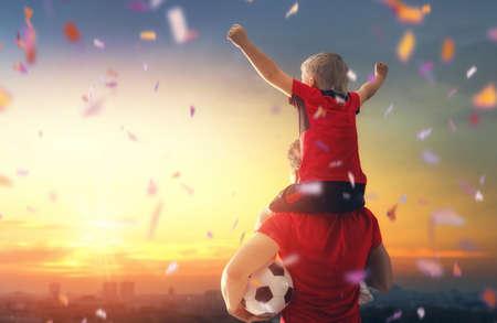 Lindo niño soñando con convertirse en jugador de fútbol. Niño con hombre jugando al fútbol en la puesta de sol. Deporte familiar.