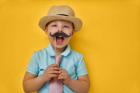 Funny time. Happy father's day! Boy playing and holding paper mustache on stick and pretending of daddy. Banque d'images
