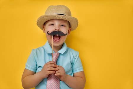Lustige Zeit. Alles gute zum Vatertag! Junge, der Papierschnurrbart auf Stock spielt und hält und Papa vortäuscht.