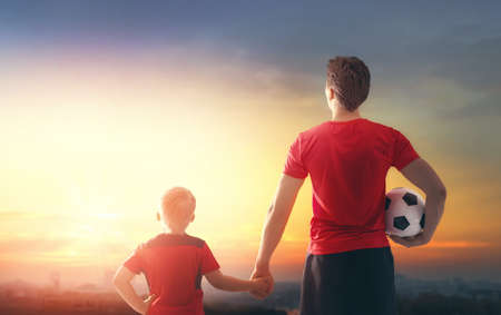 Cute little child dreaming of becoming a soccer player. Boy with man playing football on sunset. Family sport. Stock Photo