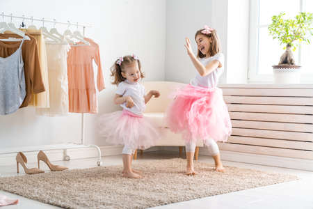 Happy girls dressing up at home. Funny lovely children are having fun in room. Archivio Fotografico