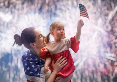 Patriotic holiday. Happy kid, cute little child girl and her mother with American flag. USA celebrate 4th of July. Stock Photo