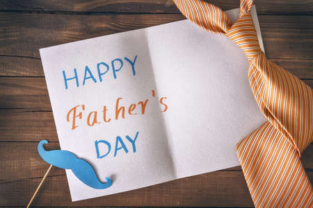 Happy fathers day! Postcard and tie on background of wooden table.