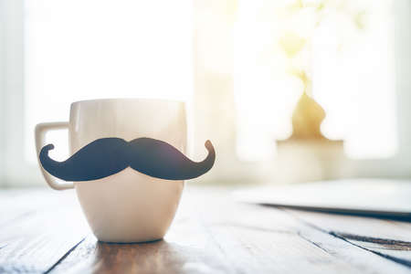 Happy fathers day! Cup of coffee on background of wooden table.