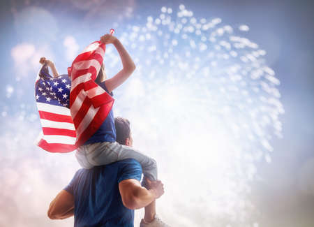 Patriotic holiday. Child sitting on shoulders of her father and  holding the Flag of the USA. America celebrate 4th of July.