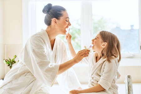 Happy family! Mother and daughter child girl are brushing teeth toothbrushes in the bathroom.