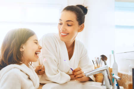 Happy family! Mother and daughter child girl are brushing teeth toothbrushes in the bathroom. Archivio Fotografico - 103091500