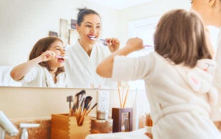 Glückliche Familie! Mutter und Tochter Kind Mädchen putzen Zähne Zahnbürsten im Badezimmer.