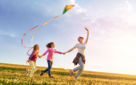 Happy family playing outdoor. Mother and children running on meadow with a kite in the summer on the nature. Stockfoto - 104432042