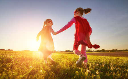 Two little children are playing superhero. Kids on the background of sunset sky. Girl power concept Stockfoto - 104432079