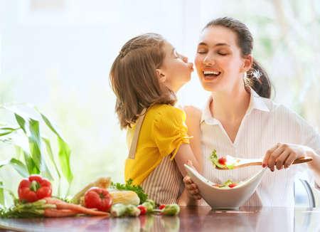 Gesundes Essen zu Hause. Glückliche Familie in der Küche. Mutter und Kind Tochter bereiten das Gemüse vor.