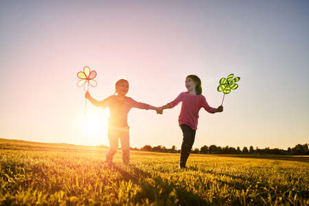 Happy kids is having fun on nature in the summer. Children are laughing and playing on meadow at sunset background. Stockfoto - 104432090