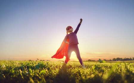 El niño pequeño está jugando al superhéroe. Cabrito en el fondo del cielo al atardecer. Concepto de poder femenino Foto de archivo