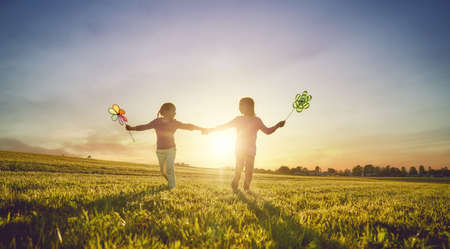Happy kids is having fun on nature in the summer. Children are laughing and playing on meadow at sunset background.
