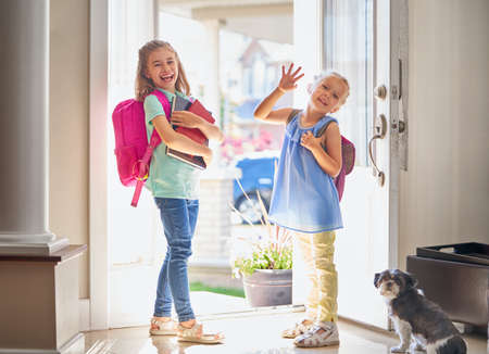 Alumnos de primaria. Las niñas con mochila van a la escuela desde casa. Inicio de lecciones. Primer día de otoño. Foto de archivo - 104771821