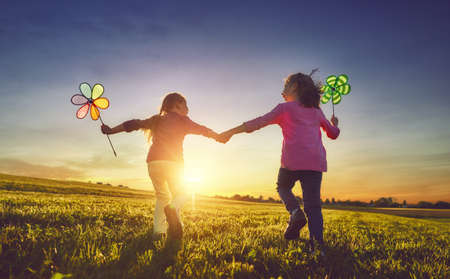 Happy kids is having fun on nature in the summer. Children are laughing and playing on meadow at sunset background. Stockfoto - 104771823