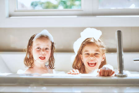 Happy children girls are bathing in a bath with foam and bubbles.