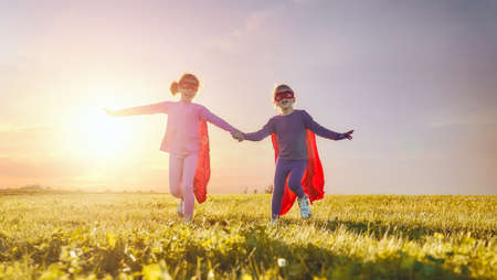 Two little children are playing superhero. Kids on the background of sunset sky. Girl power concept Stockfoto - 104771827
