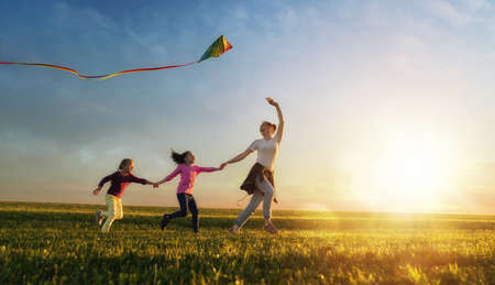 Happy family playing outdoor. Mother and children running on meadow with a kite in the summer on the nature. Stockfoto - 104771824