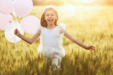 Happy kid is having fun on nature in the summer. Child is laughing and playing on meadow at sunset background. Girl with air balloons is running on cereal field.