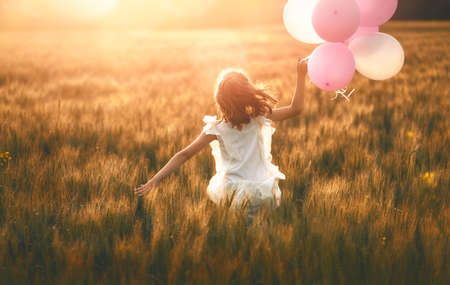 Happy kid is having fun on nature in the summer. Child is playing on meadow at sunset background. Girl with air balloons is running on cereal field.