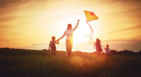Happy family playing outdoor. Mother and children running on meadow with a kite in the summer on the nature. Stockfoto - 105504184