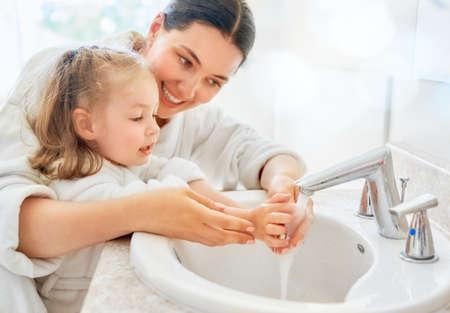 Niña linda y su madre se lavan las manos con agua corriente. Foto de archivo - 105504226