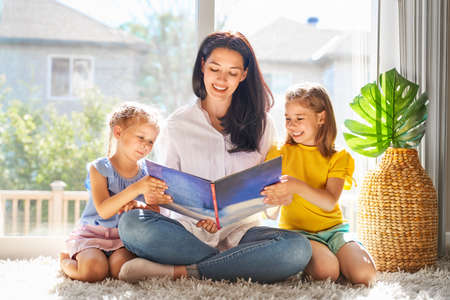 Happy loving family. Pretty young mother reading a book to her daughters Stok Fotoğraf